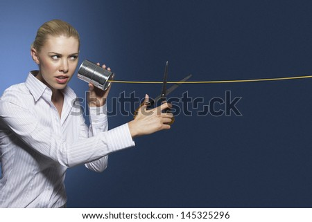 Businesswoman cutting line on tin can string phone against blue background - stock photo