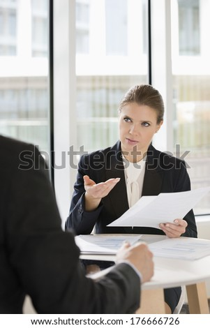 Businesswoman discussing over documents with colleague in office cafe - stock photo