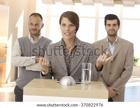 Businesswoman doing formal speech at pulpit, colleagues standing beside. - stock photo