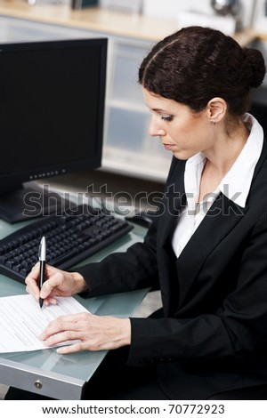businesswoman doing paperwork in an office - stock photo