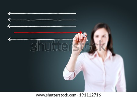 Businesswoman drawing arrows in different directions. - stock photo