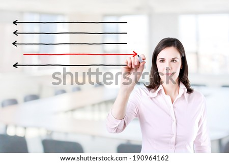 Businesswoman drawing arrows in different directions. Office background. - stock photo