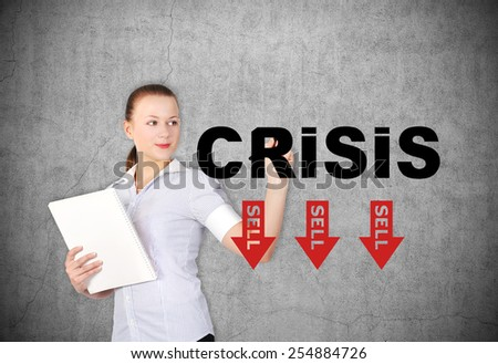 businesswoman drawing crisis symbol with sell arrow - stock photo