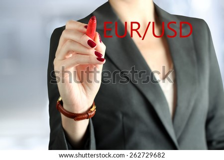 Businesswoman drawing   eur and usd on  a virtual  graph by  a  red pen  - stock photo