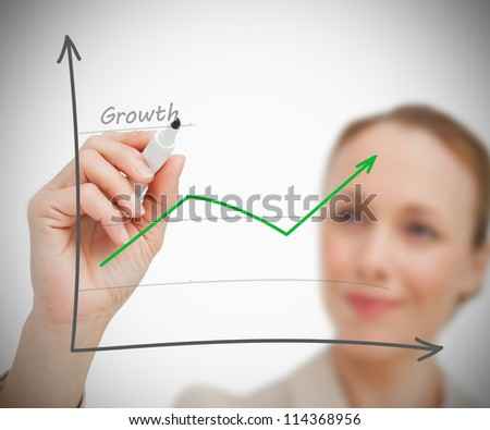 Businesswoman drawing growth graph