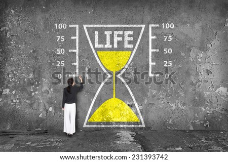 businesswoman drawing life sandglass on the wall - stock photo