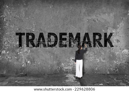 businesswoman drawing trademark on the wall