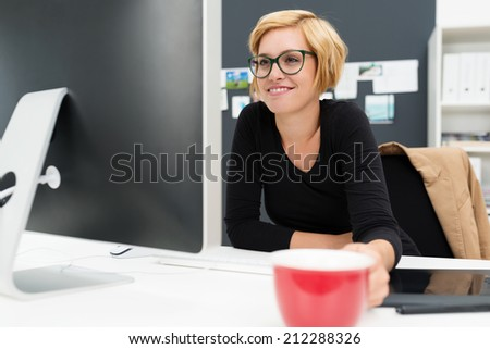 Businesswoman drinking coffee as she works holding a red cup in her hand as she reads information on her computer screen with a relaxed smile - stock photo