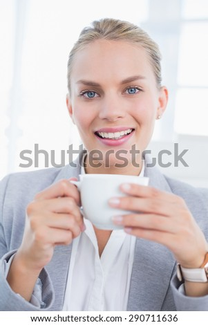 Businesswoman drinking coffee behind her computer in her office