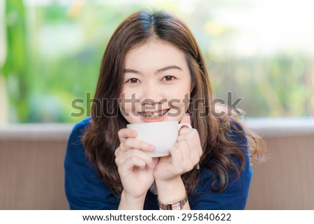 Businesswoman drinking coffee / tea and smiling in a coffee shop