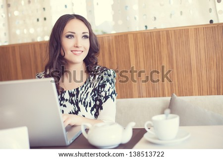 Businesswoman drinking tea and using computer in a coffee - stock photo