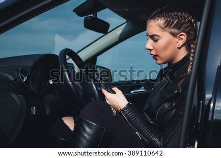Businesswoman driving car and using her mobile phone.