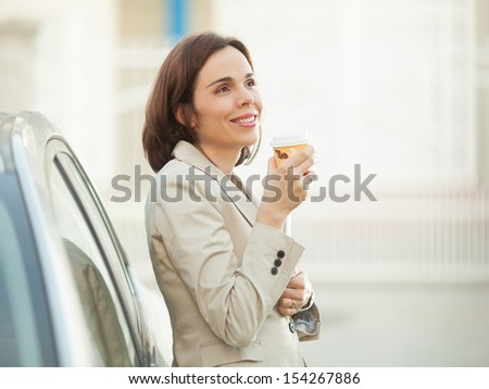 Businesswoman enjoying cup of coffee outdoors  - stock photo