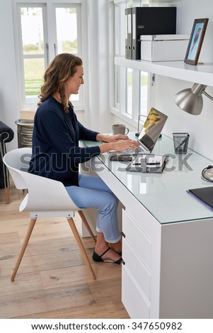 businesswoman entrepreneur working on laptop from home office space - stock photo