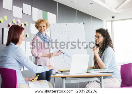 Businesswoman explaining pie chart to colleagues in creative office - stock photo