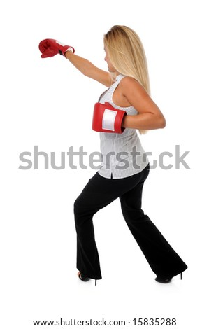 Businesswoman fighting with boxing gloves - stock photo