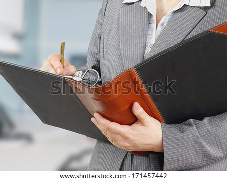 Businesswoman filling a form in documents folder