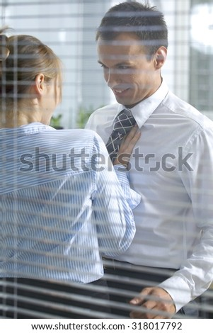 Businesswoman flirting with his colleague in office - stock photo