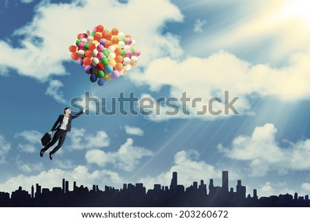 Businesswoman flying with balloons over cityscape to get success - stock photo