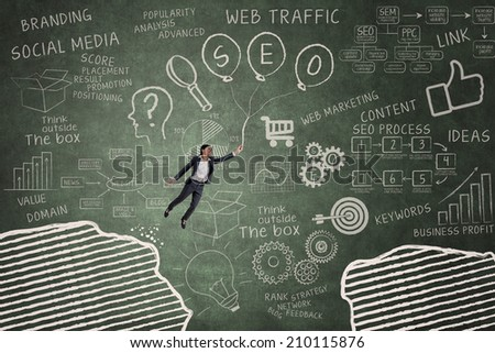 Businesswoman flying with SEO balloon through gap on the blackboard - stock photo