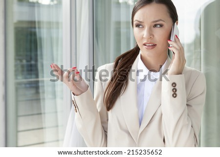 Businesswoman gesturing while answering cell phone against glass door - stock photo