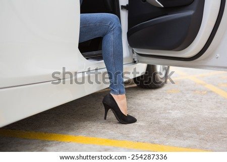 Businesswoman getting out the front door in her car - stock photo