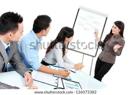 businesswoman giving a presentation to business team - stock photo