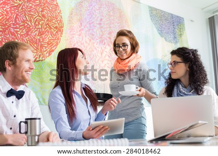 Businesswoman giving coffee to female colleague in creative office - stock photo