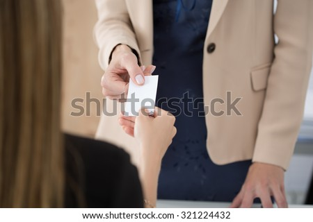 Businesswoman giving her businesscard to her partner. Business meeting, invitation, partnership or hiring concept. - stock photo