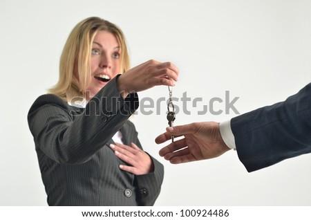 Businesswoman giving keys to businessman - stock photo