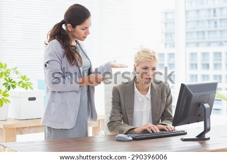 Businesswoman giving orders at her coworker in an office - stock photo