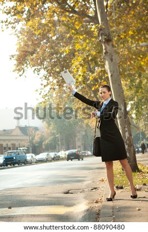 Businesswoman hailing taxi and looking in clock - stock photo