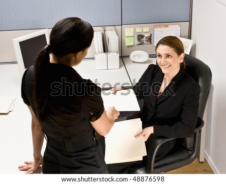 Businesswoman handing co-worker file folder - stock photo