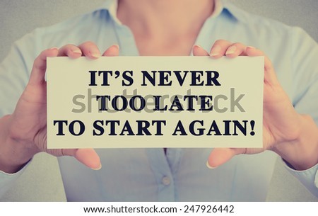 Businesswoman hands holding white card sign with It's never too late to start again text message isolated on grey wall office background. Retro instagram style image - stock photo