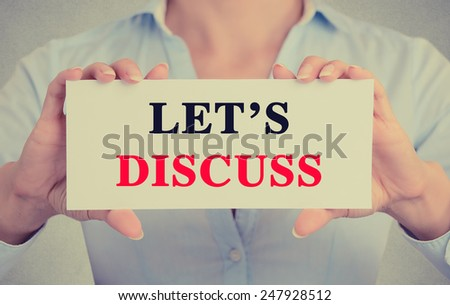 Businesswoman hands holding white card sign with let's discuss text message isolated on grey wall office background. Retro instagram style image - stock photo