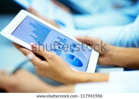 Businesswoman hands with touchpad while learning situation on the market - stock photo