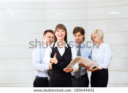 businesswoman handshake, hold hand shake welcome gesture, young excited business woman happy smile at conference hall over group of businesspeople working background, people meeting - stock photo