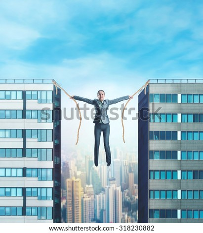 Businesswoman hanging between two skyscrapers  - stock photo