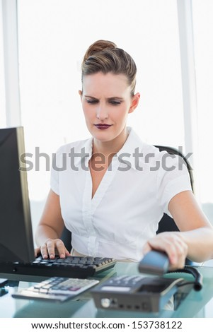 Businesswoman hanging up the phone while working in bright office - stock photo
