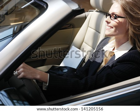 businesswoman has a fan with laptop in black car