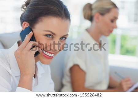 Businesswoman having a call while her colleague writing in bright office - stock photo