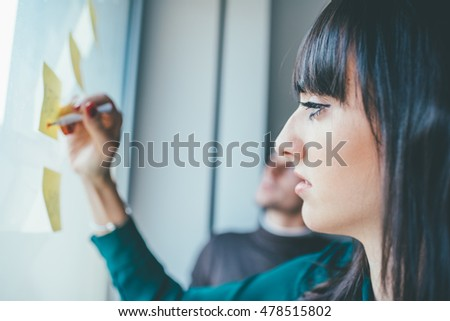 Businesswoman having a meeting in office. She is standing in front of glass wall with post it notes, pointing and discussing - business, teamwork, brainstorming concept