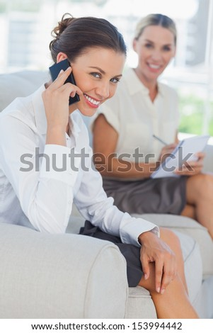 Businesswoman having a phone call while her colleague writing in bright office - stock photo