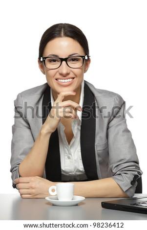 Businesswoman having coffee break, sitting at her office desk, over white background - stock photo