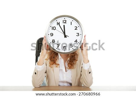 Businesswoman hiding behind clock by a desk. - stock photo