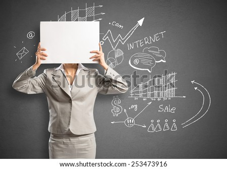 Businesswoman hiding her face behind sheet of paper