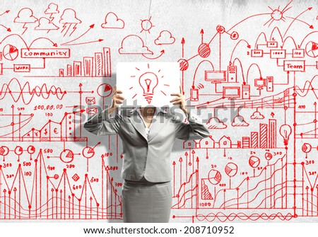 Businesswoman hiding her face with sheet of paper with sketches at background