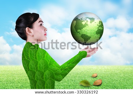 Businesswoman hold green grass global like firmly in hands over green grass field and blue sky white clouds  a nature concept for ideas development