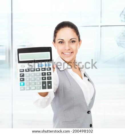 businesswoman hold show calculator, young excited business woman bookkeeper smile in modern office - stock photo