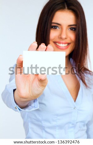 Businesswoman holding a blank card with a smile - stock photo